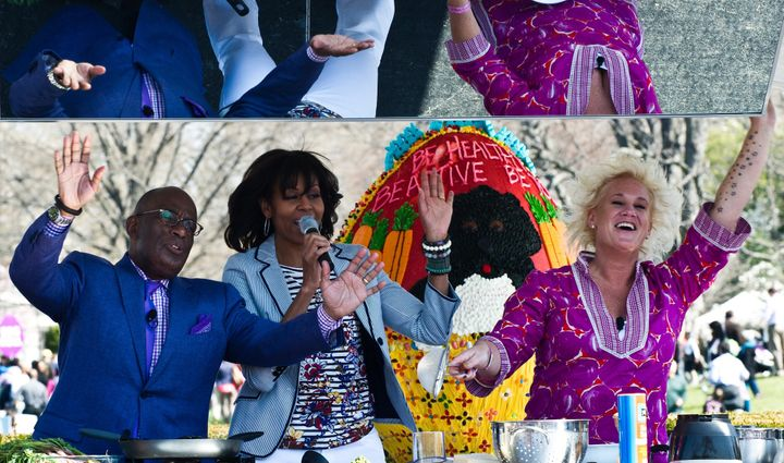 US First Lady Michelle Obama (C), chef Anne Burrell (R) and television personality Al Roker sing at a cooking station during