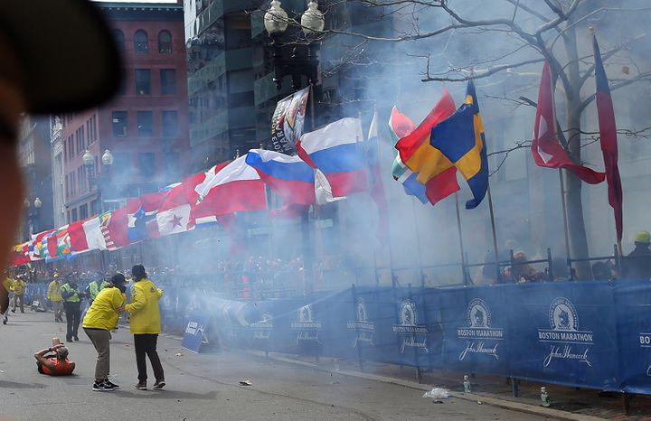 BOSTON - APRIL 15: Officials react as the first explosion goes off on Boylston Street near the finish line of the 117th Bosto