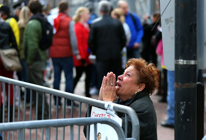 BOSTON - APRIL 15: A woman kneels and prays at the scene of the first explosion on Boylston Street near the finish line of th