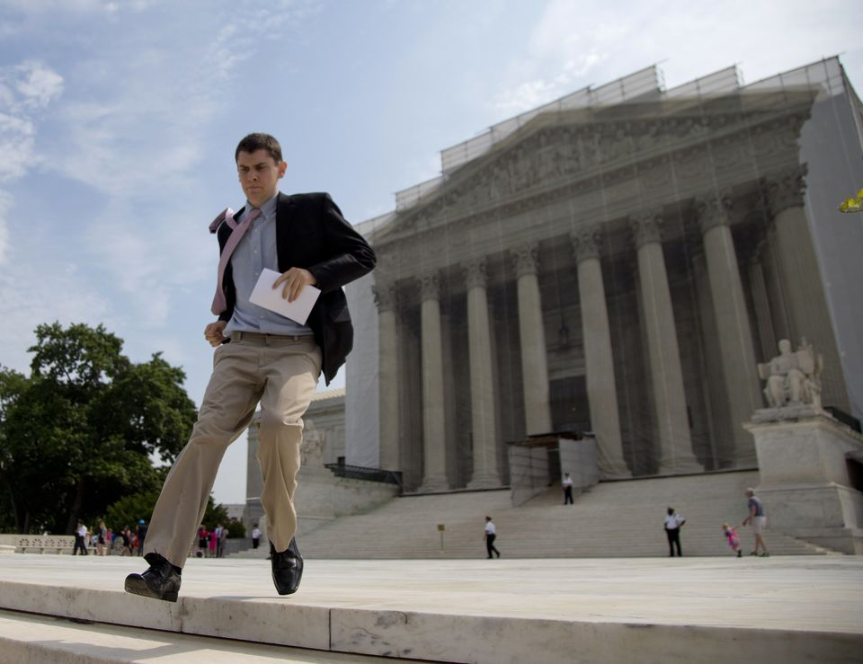 Dan Stein, an intern with the SCOTUS Blog, runs after court decisions from the Supreme Court in Washington, Monday, June 24,