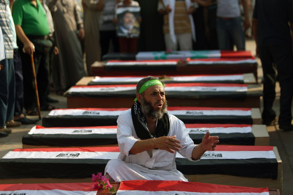 A supporter of deposed Egyptian president Mohamed Morsi sits near an empty coffins during a fake funeral in the memory of the