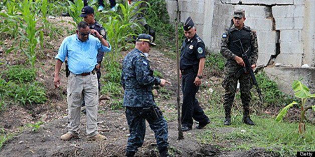 Honduran police director Juan Carlos 'El Tigre' Bonilla (C) works in the site where human remains allegedly corresponding to