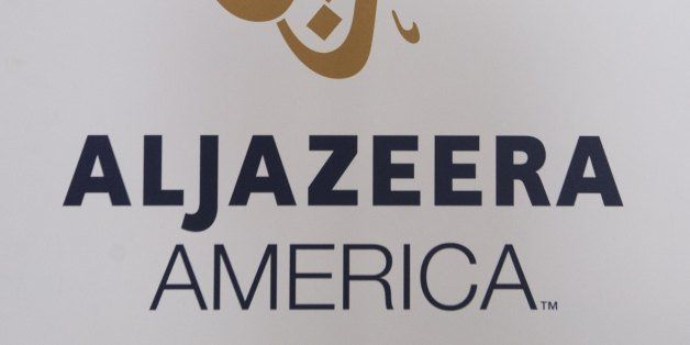 The logo for the cable news network Al Jazeera America appears outside the network's studio space at the Newseum in Washington, DC, August 16, 2013. Al Jazeera America, a cable news network set to launch on August 20, will have 12 bureaus in major cities in the US, three broadcast centers, a headquarters in New York City, and around 900 journalists and staff. AFP PHOTO / Saul LOEB (Photo credit should read SAUL LOEB/AFP/Getty Images)