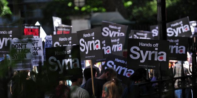 Protesters holds signs during a protest against military intervention in Syria in central London on August 31, 2013. British lawmakers voted late on August 29 to reject Prime Minister David Cameron's call for British involvement in military strikes aimed at punishing the Syrian regime for alleged chemical weapons use. AFP PHOTO/CARL COURT (Photo credit should read CARL COURT/AFP/Getty Images)