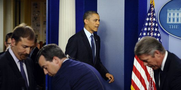 US President Barack Obama (C) arrives to give a press conference in the Brady Press Briefing Room at the White House in Washi