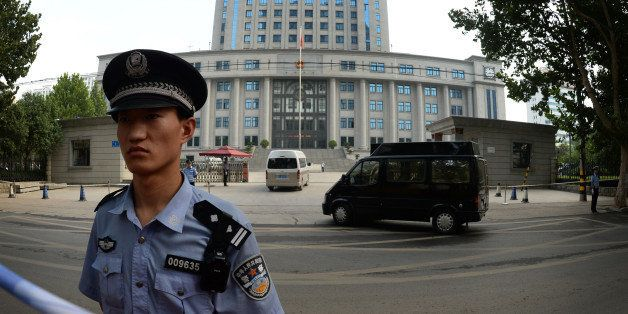 Police stand guard as officials arrive for the trial of disgraced politician Bo Xilai on the fourth day of Bo's trial at the