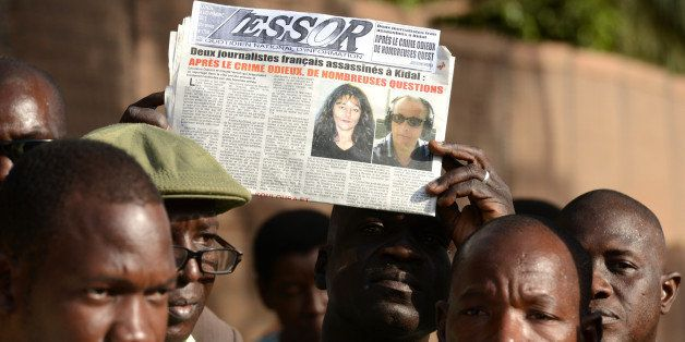 A Malian journalist holds a local newspaper showing on frontpage the portraits of Radio France Internationale (RFI) journalis