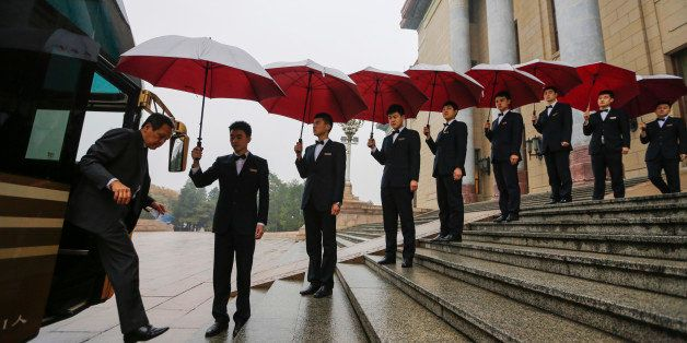 BEIJING, CHINA - NOVEMBER 1:  Attendants hold umbrellas to protect delegates from rain as they arrive for the opening ceremon