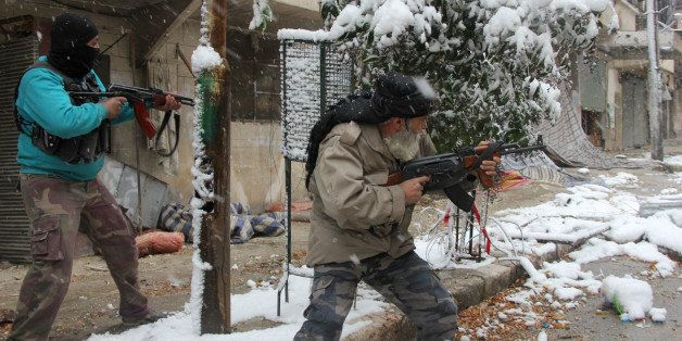 Rebel fighters hold their weapons as they stand amidst snow during clashes with Syrian pro-government forces in the Salaheddi