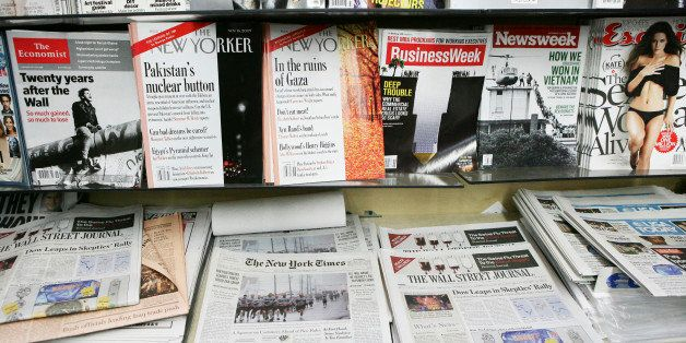 Copies of U.S. newspapers including the Wall Street Journal, New York Times, and USA Today sit on display at a news stand wit