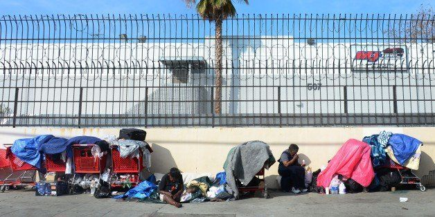 Homeless women sit amid their belongings on a street in downtown Los Angeles, California, on January 8, 2014. Poverty in the