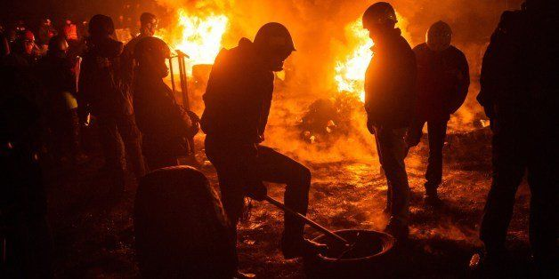 Activists of Euromaidan (the name given for Independence Square) burn tyres and warm themselves at a barricade in the center