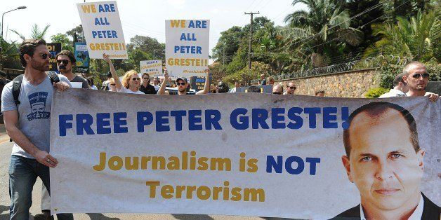 Foreign journalists hold banners bearing a picture of Peter Greste, an Australian journalist who was arrested and detained in