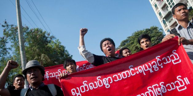 Reporters hold banners and shout slogans as they attend a demonstration march for press freedom in Yangon on January 7, 2014.