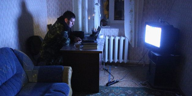 LUBIMOVKA, UKRAINE - MARCH 04:  A Ukrainian soldier inside the Belbek military base watches a television newscast in the very