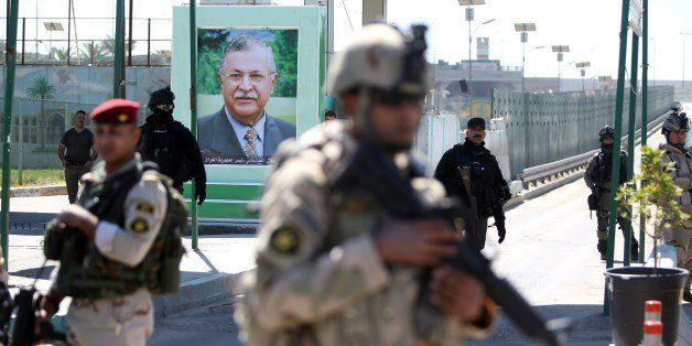 Iraqi soldiers stand guard next to a portrait of the Iraqi President at a checkpoint outside the presidential compound as the