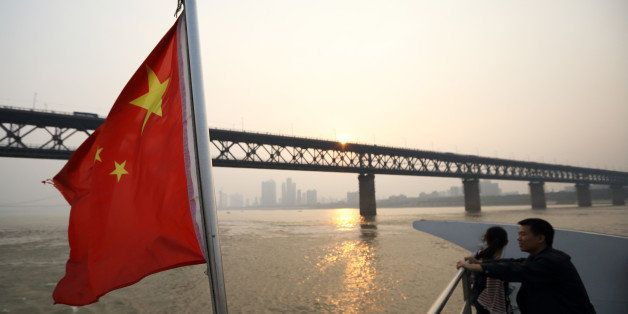 A couple stand near a Chinese national flag on a ferry crossing the Chang Jiang river in Wuhan, China, on Sunday, Oct. 20, 20