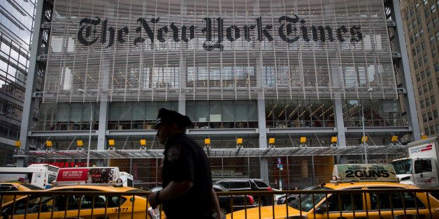 An New York City Police Department (NYPD) police officer passes in front of The New York Times Co. offices in New York, U.S.,
