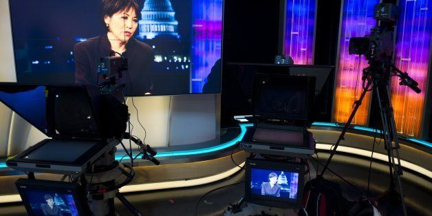 Joie Chen, host of the new Al Jazeera America nightly news program America Tonight, appears on television monitors in the net