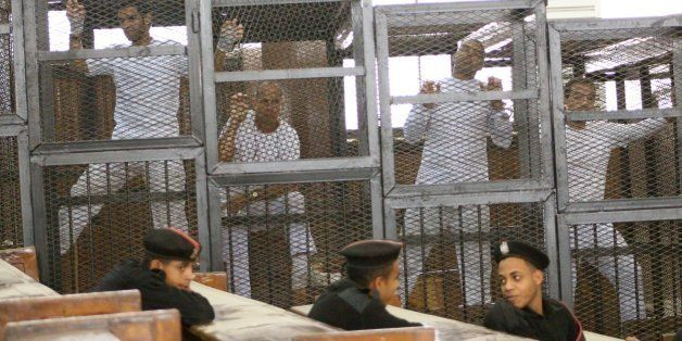Defendants in the Marriott terror cell case in Cairo stand in cages in an Egyptian courtroom Monday, March 31, 2014, as they