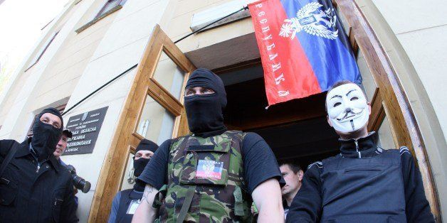 Pro-Russian activists stand guard outside a regional television station after it was seized by pro-Russian separatists, in th