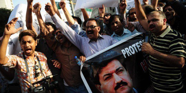 Pakistani journalist shout slogans during a protest against an attack on television anchor Hamid Mir in Karachi on April 21, 2014. A leading Pakistani journalist and TV anchor who was shot three times in an attack in Karachi is conscious and in stable condition, a spokesman from the hospital where he is being treated said. Hamid Mir, who hosts a prime-time current affairs talk show on the Geo News channel, was attacked while travelling by car to his office from the airport in Karachi. AFP PHOTO/Asif HASSAN (Photo credit should read ASIF HASSAN/AFP/Getty Images)