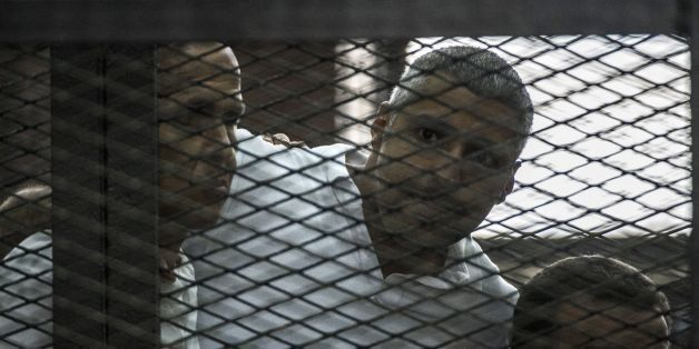 Al-Jazeera news channel's Australian journalist Peter Greste (L) and his colleagues, Egyptian-Canadian Mohamed Fadel Fahmy (C