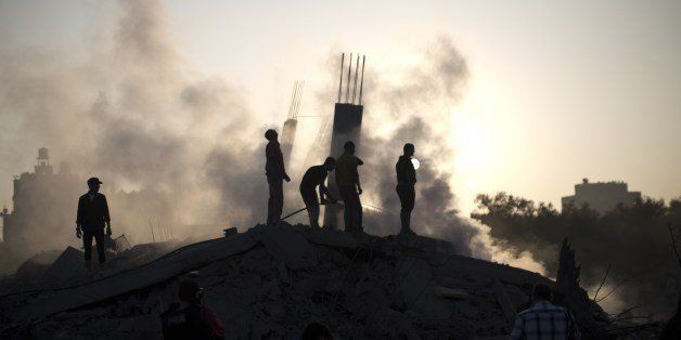 Palestinian men inspect the site of an Israeli military strike in  Gaza City on July 08, 2014 . The Israeli air force launche