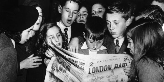 Young Scottish 'seavacuees', exiled to America for safety, eagerly catching up with news of the War in the 'Daily Mirror' aft