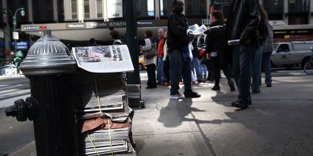 NEW YORK, NY - APRIL 16:  A newspaper vendor hands out free copies of The New York Daily News ouside of Penn Station on April