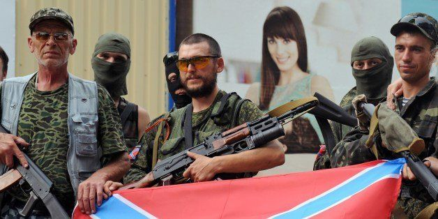 Pro-Russian militants pose on July 13, 2014 with the new Russia (novorossiya) flag in Donetsk, eastern Ukraine. Escalating cl