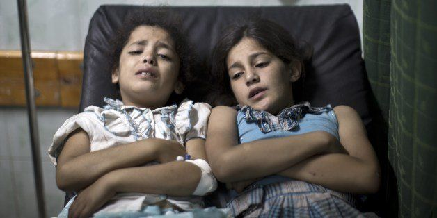 Palestinian girls who were wounded in an Israeli strike on a compound housing a UN school in Jabalia refugee camp in the northern Gaza Strip, wait for treatment at the Kamal Edwin hospital in Beit Lahia where victims from the attack were brought early on July 30, 2014. Israeli bombardments early on July 30 killed 'dozens' Palestinians in Gaza, including at least 16 at a UN school, medics said, on day 23 of the Israel-Hamas conflict. AFP PHOTO / MAHMUD HAMS (Photo credit should read MAHMUD HAMS/AFP/Getty Images)