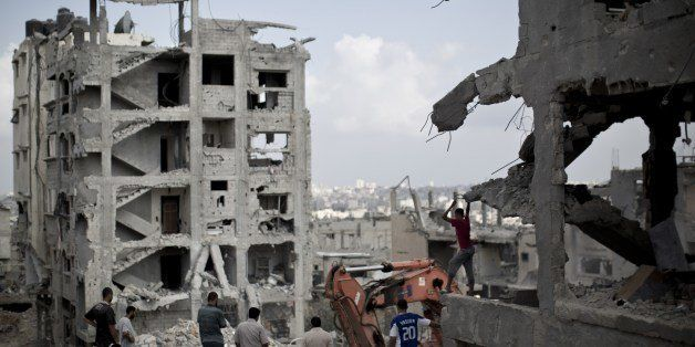 Palestinian men inspect the destruction in part of Gaza City's al-Tufah neighbourhood as the fragile ceasefire in the Gaza St