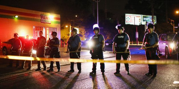 FERGUSON, MO - AUGUST 11:  Police lock down a neighborhood on August 11, 2014 in Ferguson, Missouri. Police responded with te