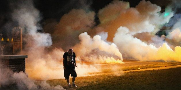 FERGUSON, MO - AUGUST 13:  Demonstrators, protesting the shooting death of teenager Michael Brown, flee as police shoot tear