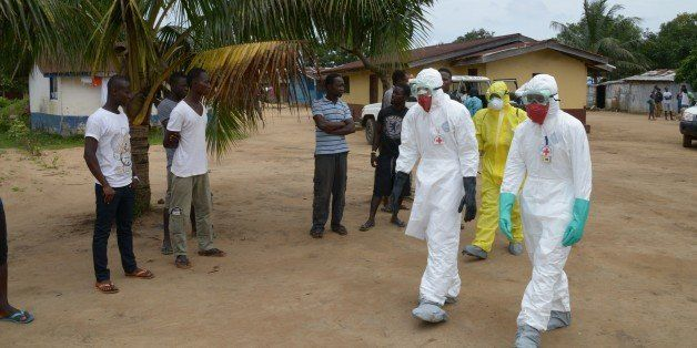 Inhabitants of the small city of Banjol, where three people inficted by Ebola virus died today, look at look at medical worke