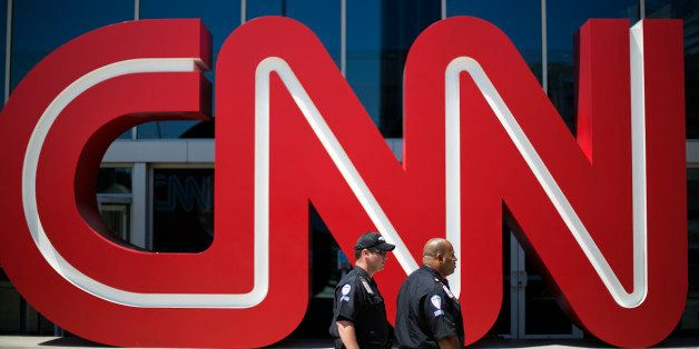 Security guards walk past the entrance to CNN headquarters, Tuesday, Aug. 26, 2014, in Atlanta. The corporate parent of CNN,
