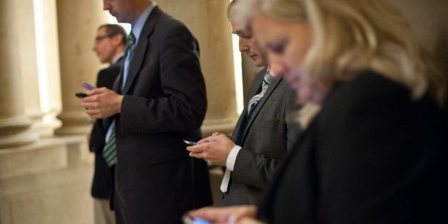 Reporters check their smartphones while waiting outside US House Speaker John Boehner's office at the US Capitol in Washingto