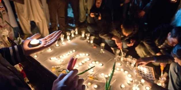 Friends and family of slain Afghan AFP reporter Sardar Ahmad attend a candle light vigil on a hill overlooking Kabul on March