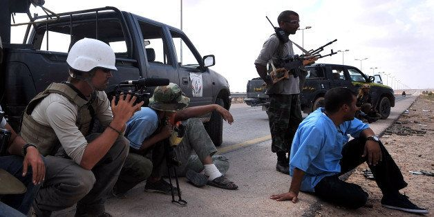 A photo taken on September 29, 2011 shows US freelance reporter James Foley (L) on the highway between the airport and the We