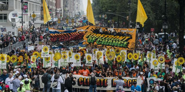 Demonstrators hold signs on a street next to Central Park during the People's Climate March in New York, U.S., on Sept. 21, 2