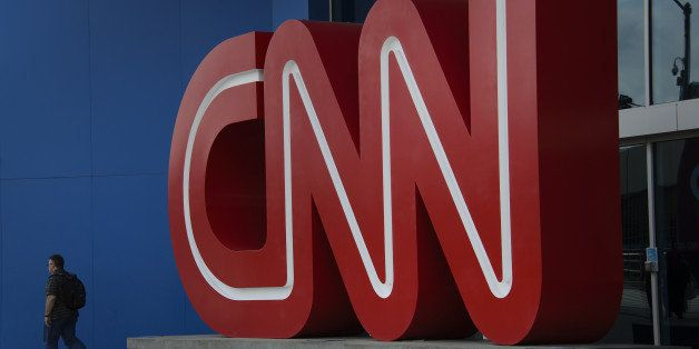 A pedestrian passes in front of CNN signage displayed at the network's headquarters building in Atlanta, Georgia, U.S., on Fr