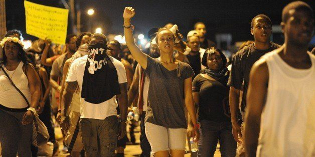 Protesters walk take part in a peaceful protest down a street in Ferguson, Missouri on August 19, 2014. Police lowered their