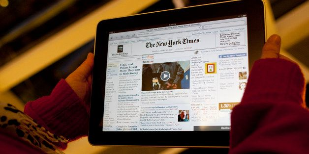 An Apple Inc. iPad tablet computer with the New York Times website displayed is held up for an illustration in New York, U.S.