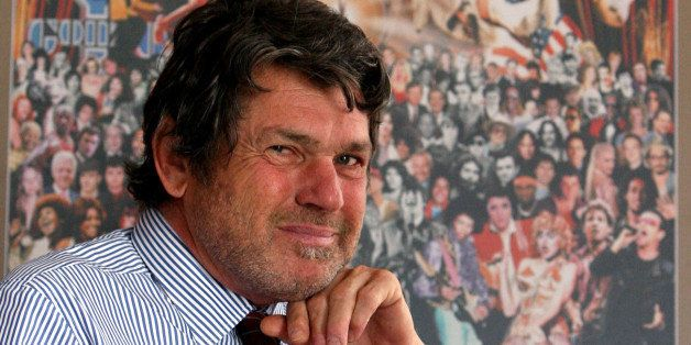 Rolling Stone publisher Jann Wenner poses for a portrait with a reproduction of the cover of the magazine's 1000th issue, Tuesday, May 2, 2006 in his New York office. (AP Photo/Mary Altaffer)
