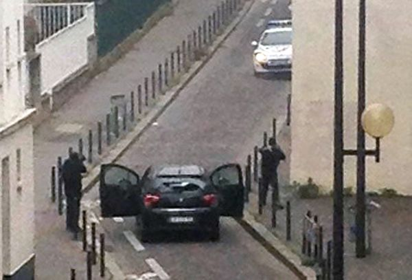 Armed gunmen face police officers near the offices of the French satirical newspaper Charlie Hebdo in Paris on January 7, 201