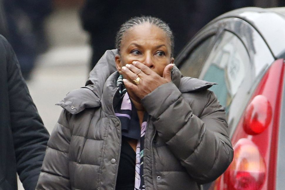 French Justice Minister Christiane Taubira reacts outside of the headquarters of the French satirical newspaper Charlie Hebdo