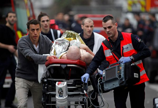 An injured person is evacuated outside the French satirical newspaper Charlie Hebdo's office, in Paris, Wednesday, Jan. 7, 20