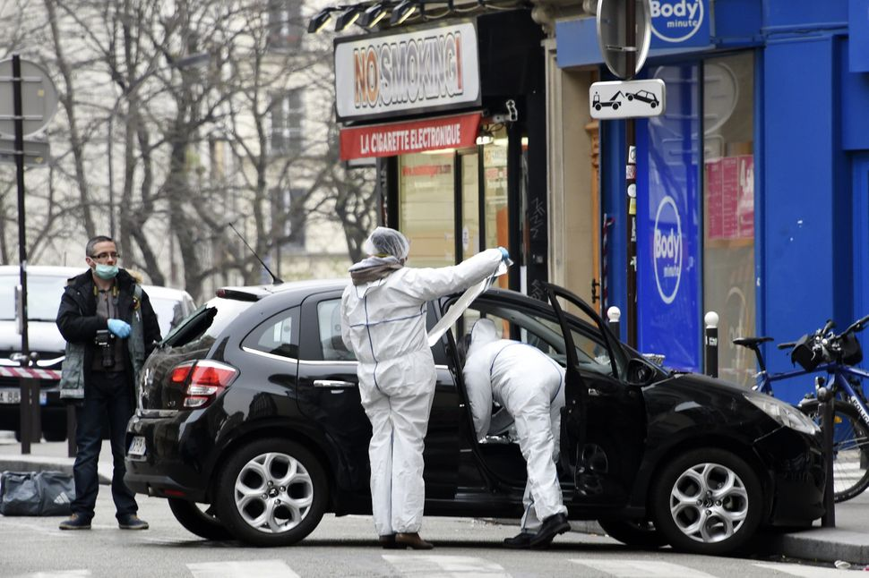 French police officers and forensic experts examine the car used by armed gunmen who stormed the Paris offices of satirical n