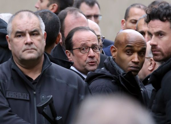 French President Francois Hollande, center, flanked with security forces arrives outside the French satirical newspaper Charl